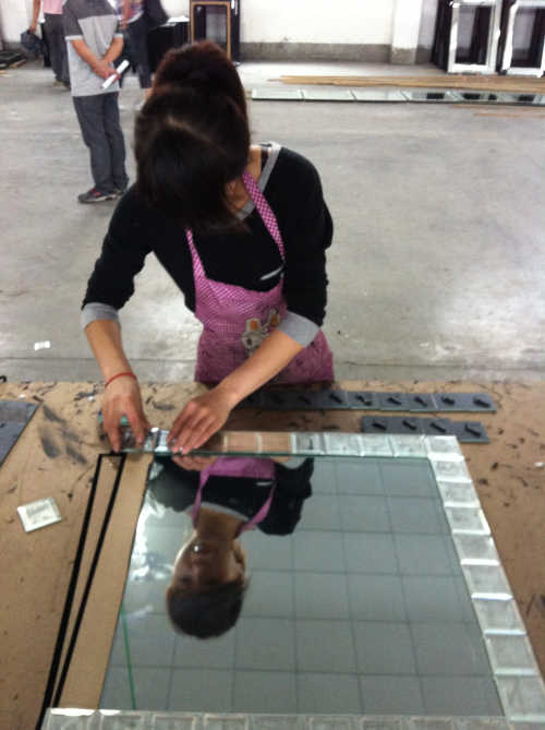 Woman at a factory assembling the outer part of a mirror