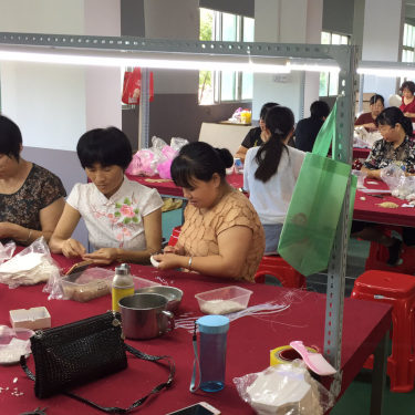 A group of women sitting at a table and working in a factory