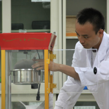 Man in lab coat examining a popcorn machine