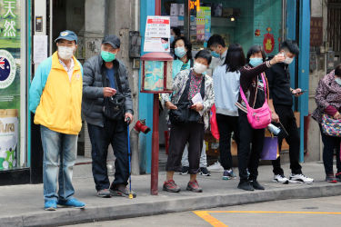 People at a bus stop in Macau wearing surgical masks
