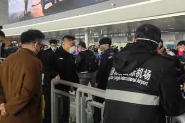 Crowd of people wearing masks at Changchun Longjia Airport security checkpoint