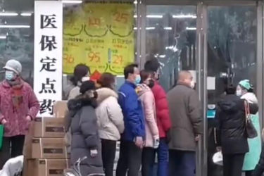 Citizens of Wuhan line up outside a drugstore wearing surgical masks