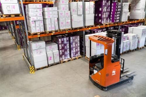 Forklift in warehouse full of cartons