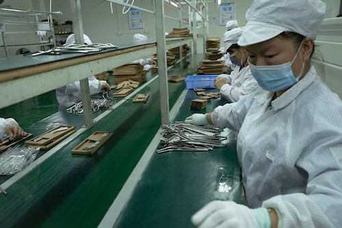 Woman working in factory before Chinese New Year factory shutdown 2022