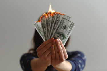 Young woman holding burning cash