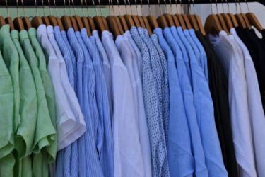 Blue and green shirts hanging on a rack