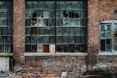 The outside of an abandoned warehouse with broken windows