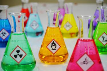 Various colorful chemicals inside Erlenmeyer flasks