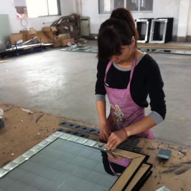 Woman assembling mirror at a factory