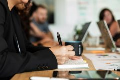Woman writing in notebook during meeting