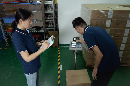 Inspectors verifying carton weight and recording it on a quality control checklist