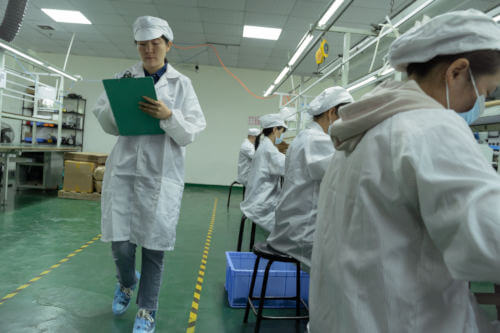 Insight auditor walking a factory with her clipboard during a factory audit