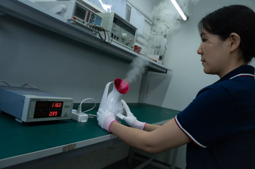 Insight employee examining a facial steamer during a product inspection