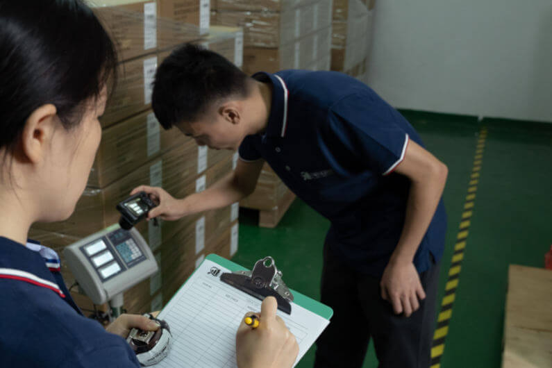Inspectors weighing cartons for inspection